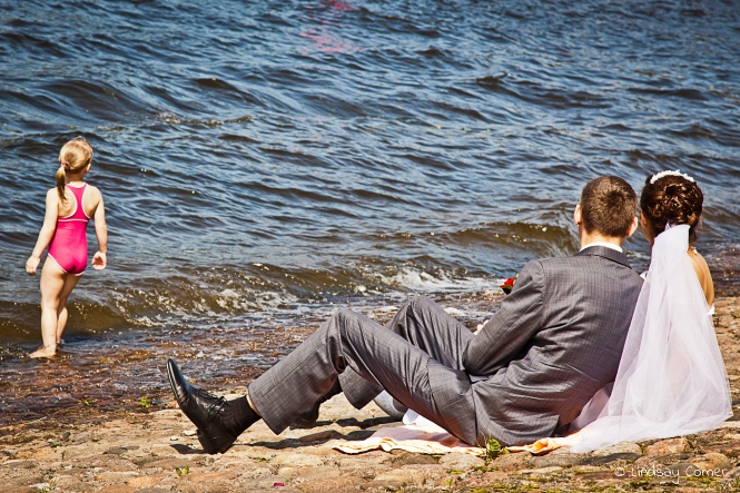 Newlyweds sitting by the river on Zayachiy Ostrov; Saint Petersburg, Russia.