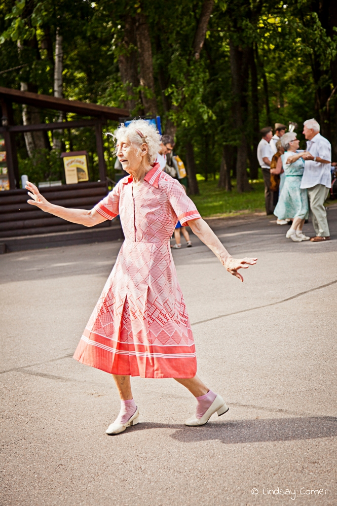 A babushka dancing on a summer afternoon in a park; Yelagin Ostrov, Saint Petersburg, Russia.