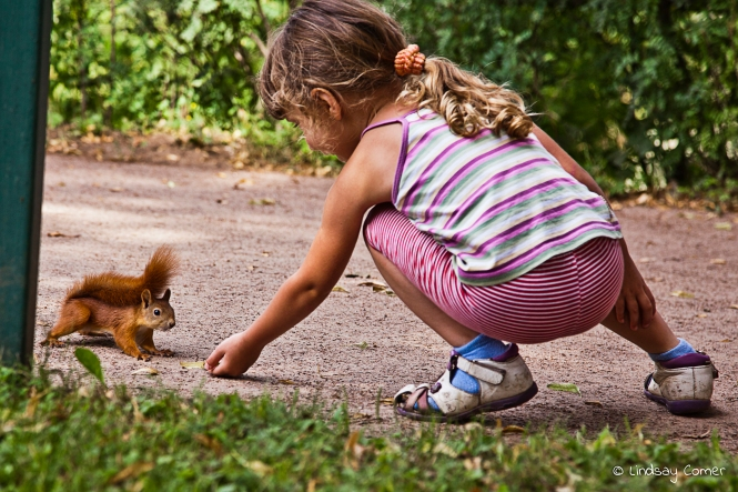 A little Russian girl trying to feed candy to a squirrel in the park at Pavlovsk; Saint Petersburg, Russia.