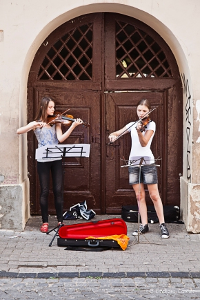 two young females playing the violin on the streets of Vilnius, Lithuania.