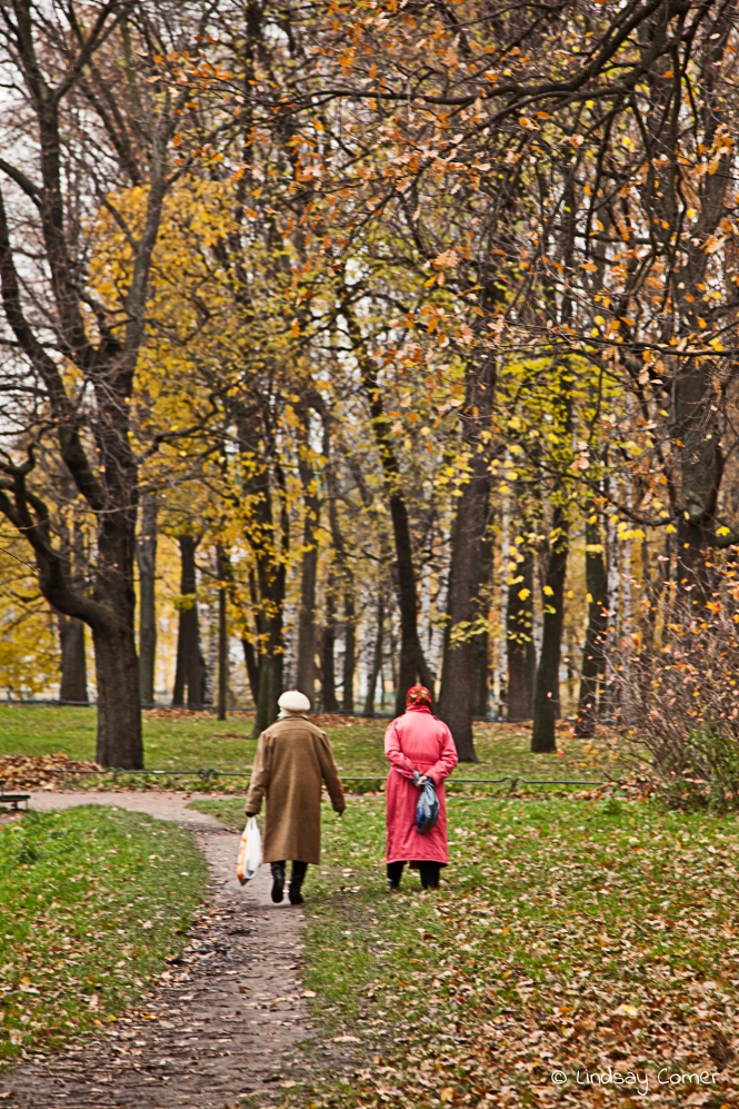 Two babushkas walking in Tavricheskiy Sad in autumn; Saint Petersburg, Russia.