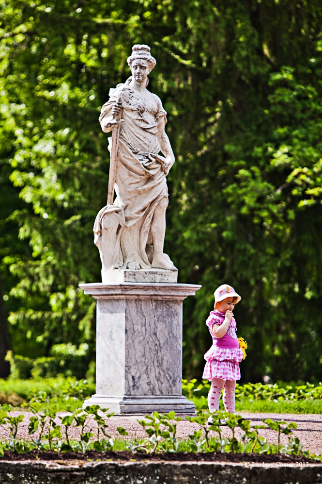 the little girl having her photo taken in front of a statue at Pavlovsk Park.