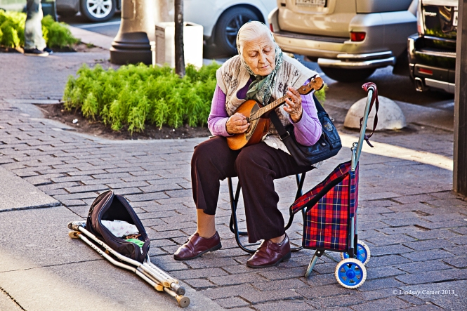 a babushka playing a domra on the sidewalk in Saint Petersburg, Russia.