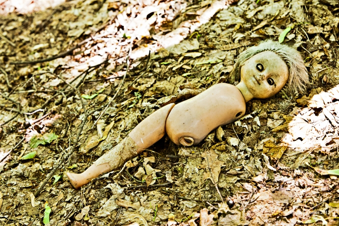 an old doll on the ground outside the abandoned children's school.