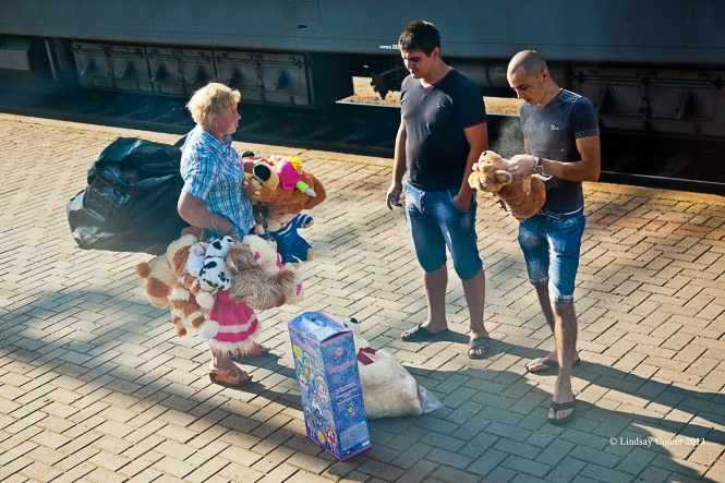 the woman selling her stuffed animals to two young men at the long train stop.