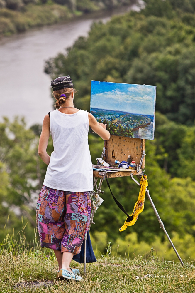 a young woman painting outside the Svensky Monastery in Bryanks, Russia.