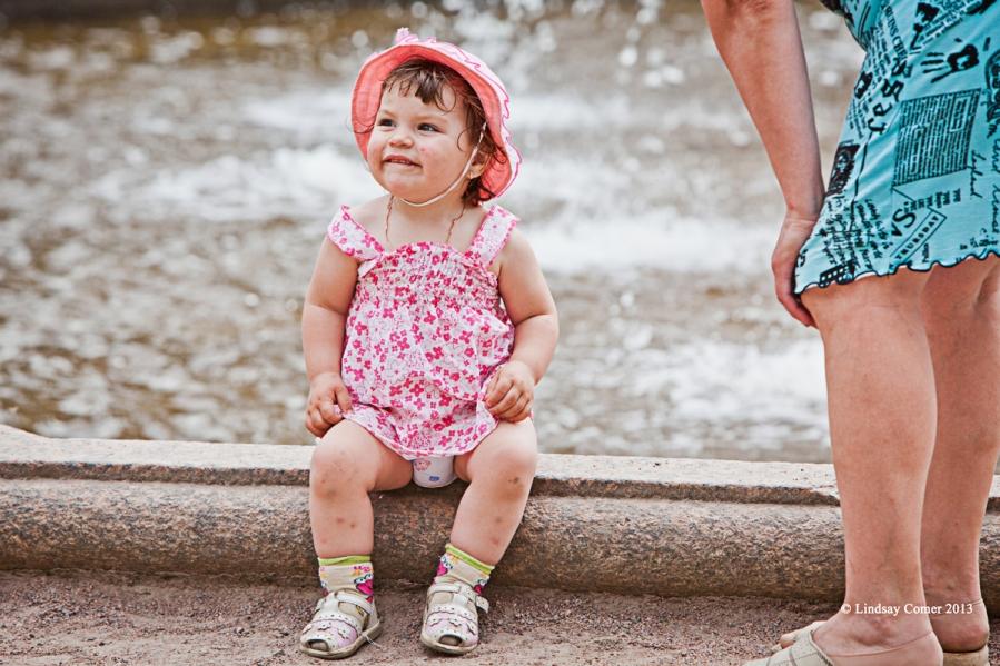 a little girl sitting near a fountain.