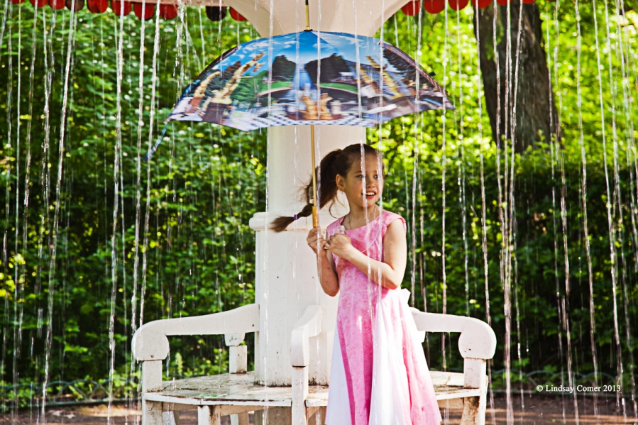 a little girl playing under a fountain.