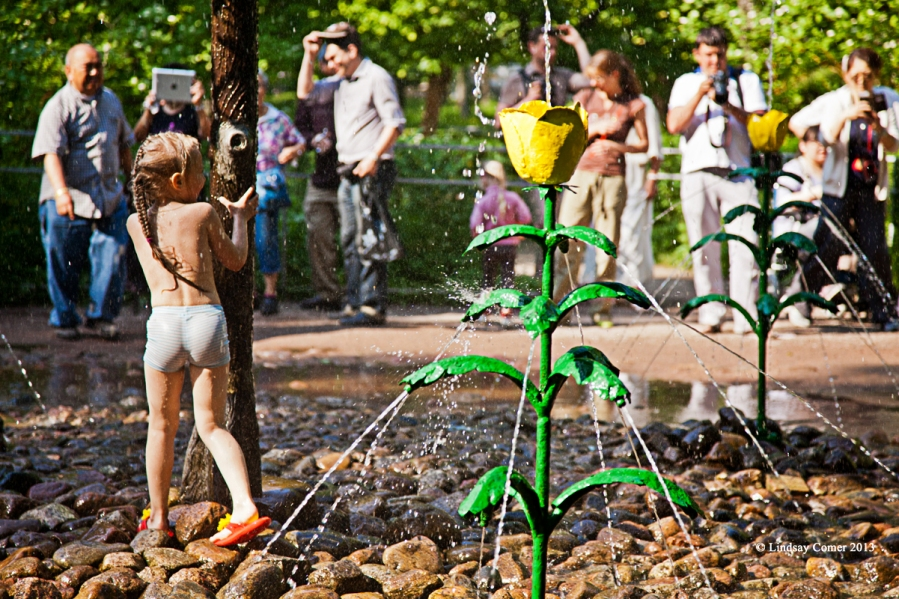 a little girl getting soaked playing near the water-squirting rose garden.